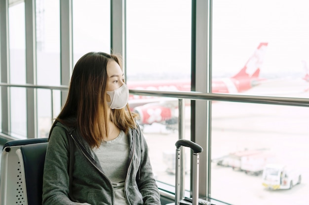 Young asian woman with surgical mask face protection sitting at the airport terminal. protection coronavirus/ covid-19 and air pollution pm2.5 concept.