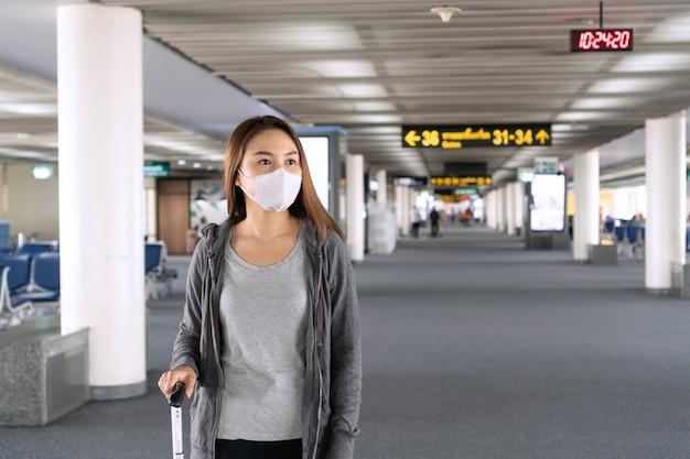 Молодая азиатская женщина с защитой стороны хирургической маски идя на крупный аэропорт. концепция здравоохранения и защиты.