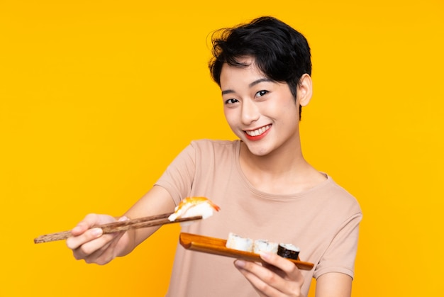 Young asian woman with sushi over yellow background