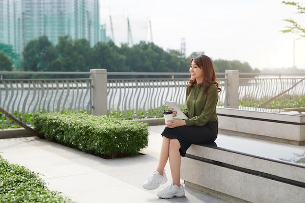 Молодая азиатская женщина с планшетным серфингом в интернете на скамейке в парке