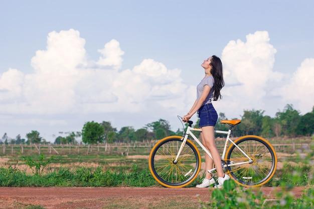 Молодая азиатская женщина с винтажным велосипедом в ландшафте природы сельской местности.