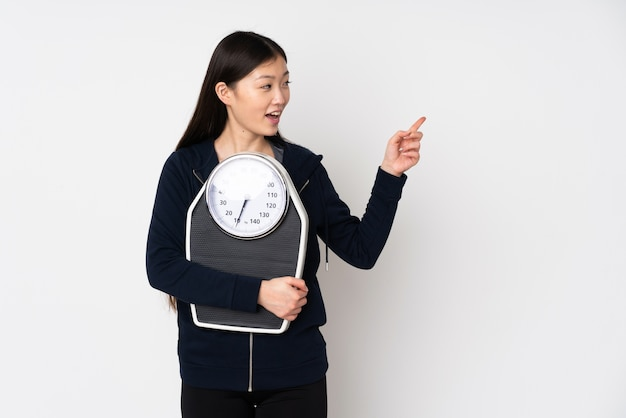Young asian woman with weighing machine and pointing side