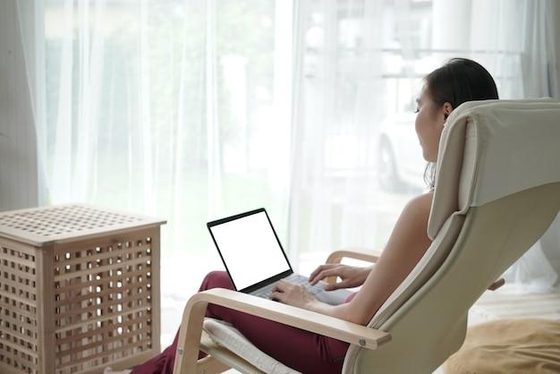 젊은 아시아 여성은 프리랜서 전자 학습 개념으로 노트북으로 집에서 일합니다.