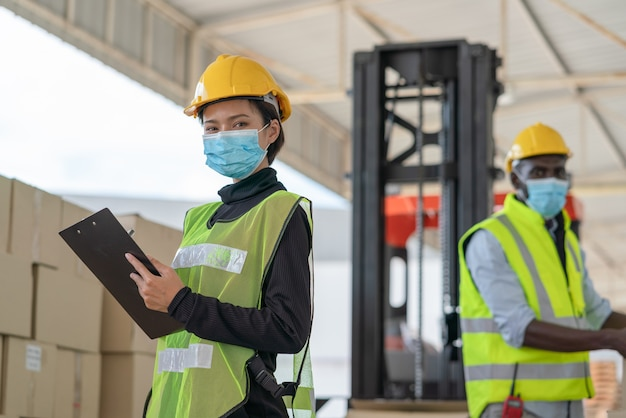 Young asian woman worker with man workers wear face mask for protect coronavirus working at logistics warehouse factory