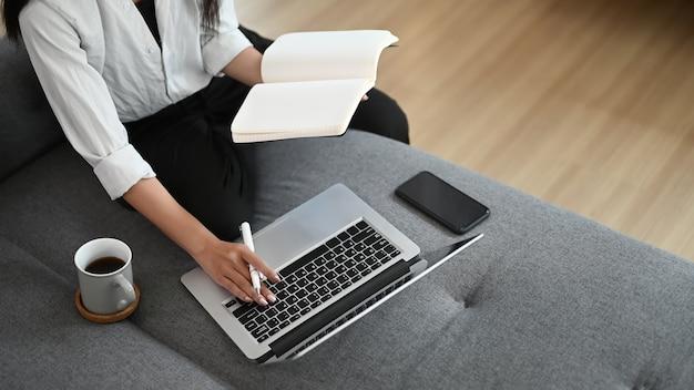 ラップトップで自宅で働く若いアジアの女性
