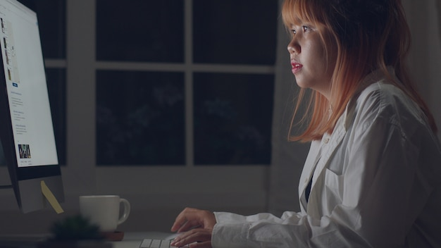 Young asian woman working late using desktop on desk in living room at home