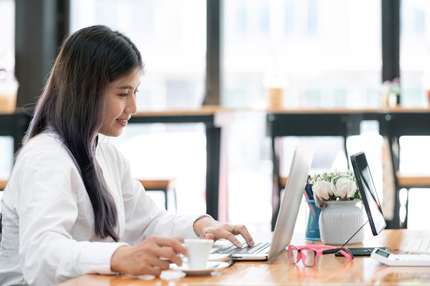 Молодая азиатская женщина работая на портативном компьютере с счастьем пока сидя за столом офиса.