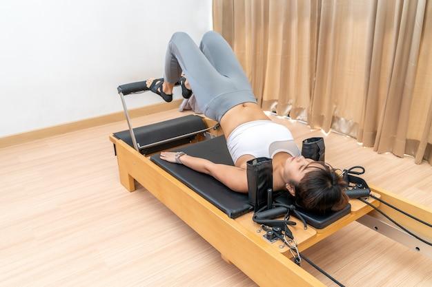 彼女の健康運動トレーニング中にピラティスリフォーマーマシンに取り組んでいる若いアジアの女性