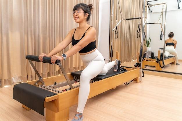 그녀의 건강 운동 훈련 중 필라테스 개혁 기계에서 작업하는 젊은 아시아 여성