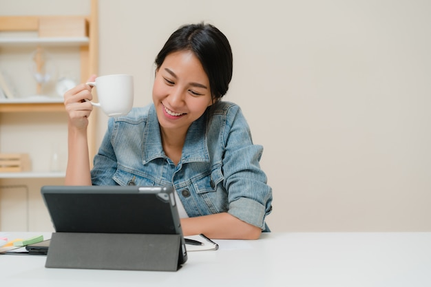 Young asian woman working using tablet checking social media and drinking coffee while relax on desk in living room at home.