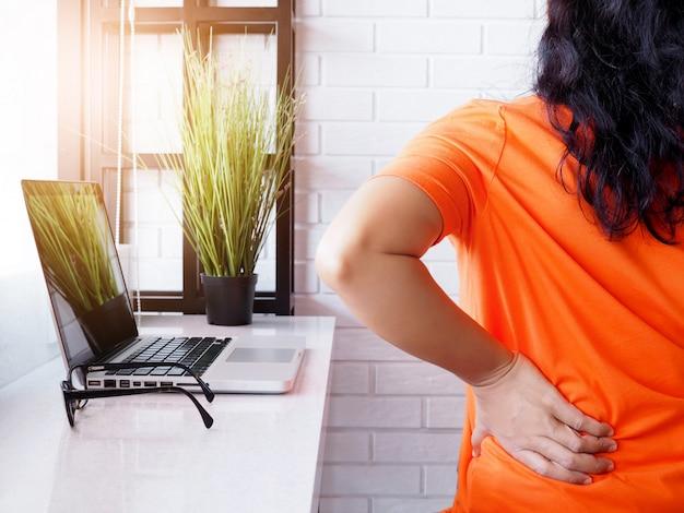 Молодая азиатская женщина работая с портативным компьютером и сидя на стуле и страдая боли в спине низкого позвоночника и рана талии, концепция здоровья и боли в теле.