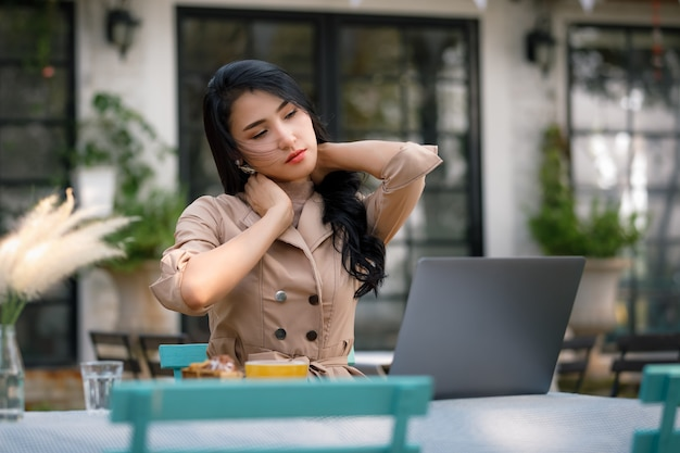 Young asian woman working with laptop computer  in garden and having neck pain