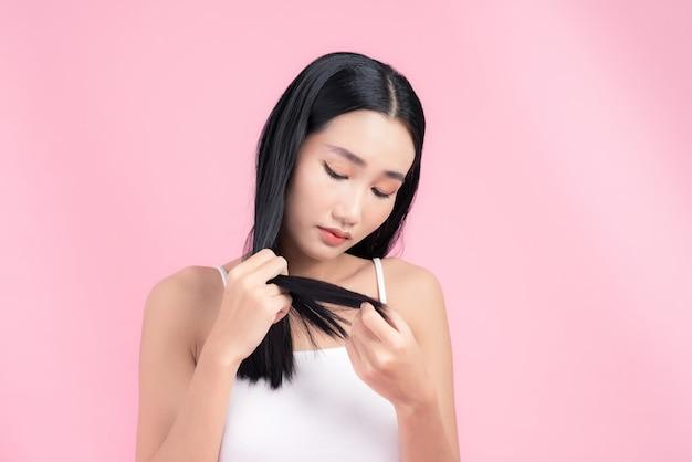 젊은 아시아 여자는 그녀의 머리에 대해 걱정. 핑크에 고립.