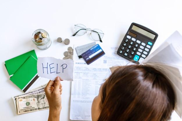 心配している若いアジアの女性は家でのストレスで助けを必要としています、会計上の負債は銀行の書類経費を請求し、支払いは悪い財政状況で必死に感じています。上面図