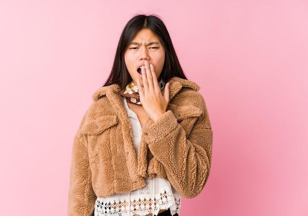 Молодая азиатская женщина, зевая, показывая усталый жест, охватывающий рот рукой.