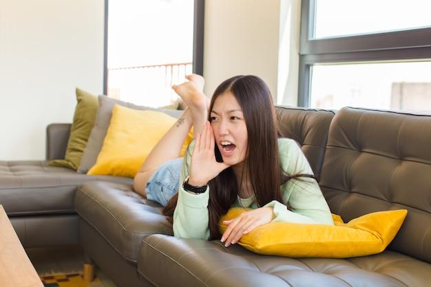 입 옆에 손으로 측면에 공간을 복사하기 위해 큰 소리로 화가 나서 고함을 지르는 젊은 아시아 여성