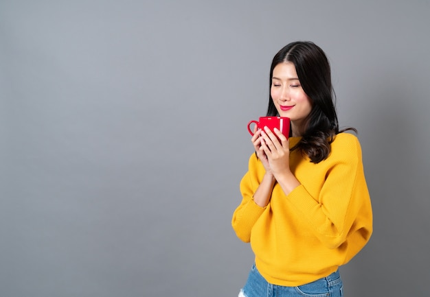 Young asian woman in yellow sweater holding a red cup of coffee, smell good and enjoy the coffee on grey wall