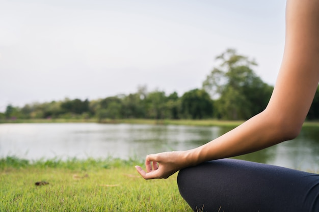 Young asian woman yoga outdoors keep calm and meditates while practicing yoga
