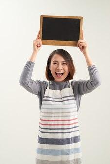 白い背景の上の空白の黒板メニューを保持している若いアジアの女性バリスタ