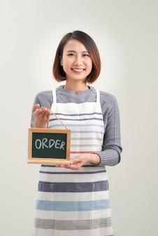 白で黒板メニューを保持している若いアジアの女性バリスタ