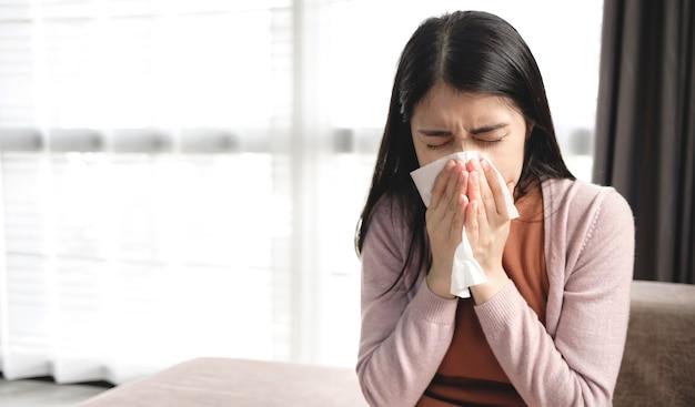 젊은 아시아 여성들은 독감, 기침 및 재채기 동안 바이러스 확산을 방지하기 위해 조직으로 입과 코를가립니다.