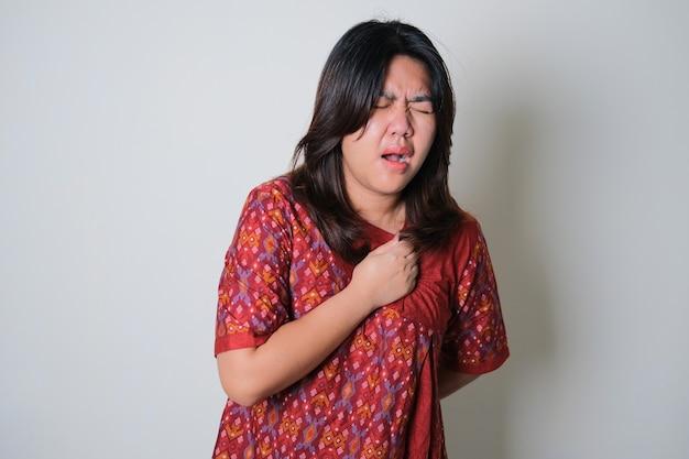 젊은 아시아 여성은 가슴 통증 제스처가 좋지 않습니다.