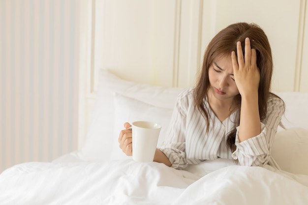 Young asian women have fever, headache, migraine, tired or stress. health and sick people concept.
