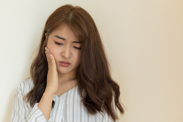 Young asian women have sensitive teeth, toothache, tooth decay or inflamed gums on clear background. health and sick people concept.