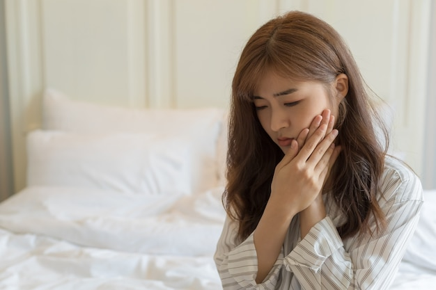 Young asian women have sensitive teeth, toothache, tooth decay or inflamed gums. health and sick people concept.