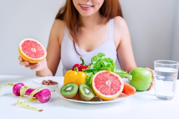 果物とオレンジと緑のリンゴを保持している若いアジアの女性