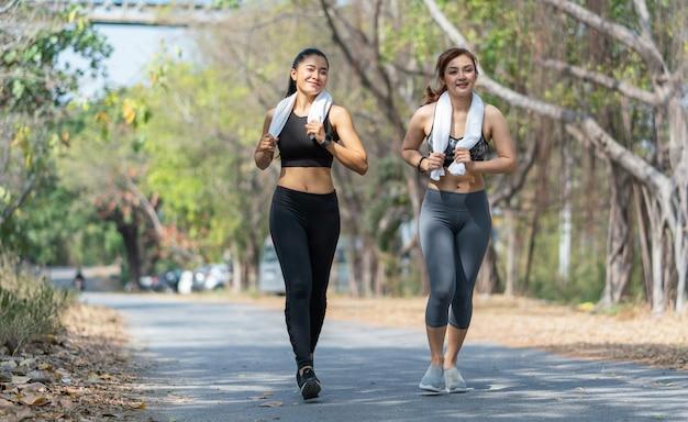 Молодые азиатские женщины в спортивной одежде бегают трусцой и бегают на открытом воздухе