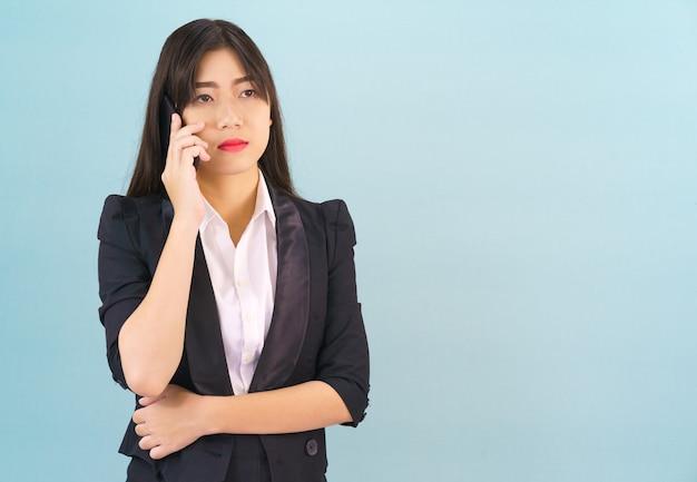 青い背景に対して彼女の電話を使用してポーズをとって立っているスーツの若いアジアの女性