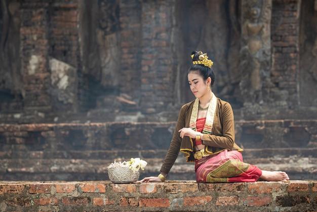 伝統的なドレスの若いアジア女性は古い壁の外観と銀の弓otロータスに座っています。伝統的な衣装の美しい女の子。レトロなタイのドレスのタイの女の子。