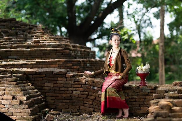 伝統的なドレスの若いアジアの女性は、古い壁に座ってロータスの横にある他の方法で見る。伝統的な衣装の美しい女の子。レトロなタイのドレスのタイの女の子。
