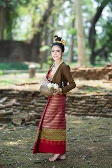 ロータスの弓を手に古い壁に立っている伝統的なドレスの若いアジア女性。伝統的な衣装の美しい女の子。レトロなタイのドレスのタイの女の子。