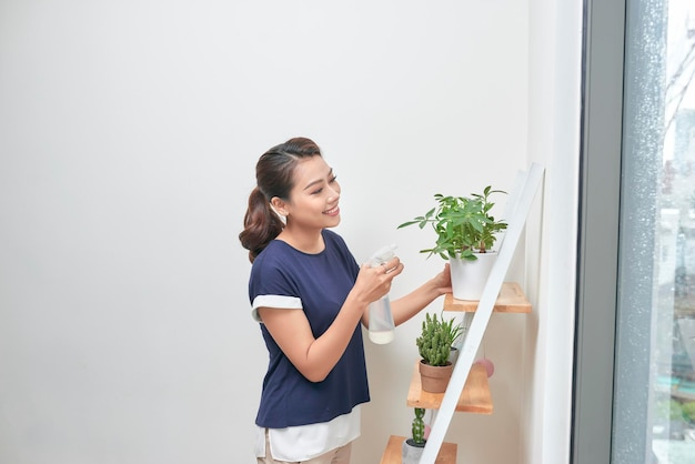 若いアジアの女性は植物に水を上げます