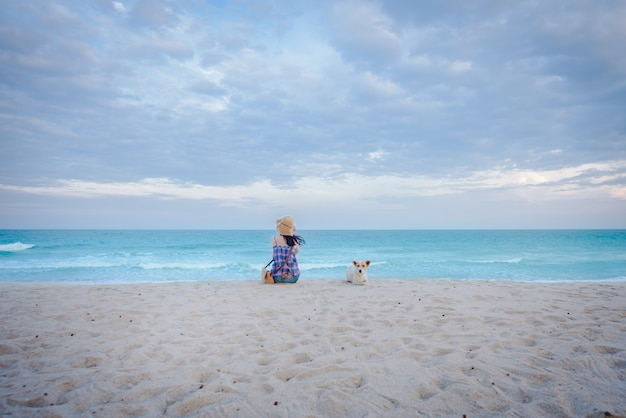 Young asian women sit sadly at the beach by the sea with a dog, sitting on the beach in the background