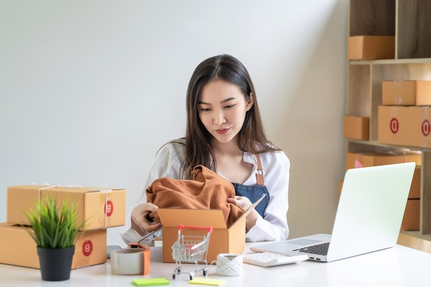 若いアジアの女性の中小企業の所有者は、自宅のラップトッププレースデスクを顧客に届けるためにオンラインで梱包しています。