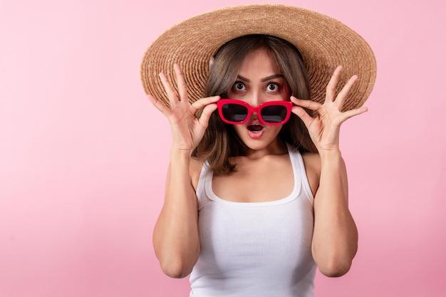 つば広の麦わら帽子と赤いサングラスをかけている若いアジア女性観光客。彼女は驚きを表明した。ピンクの背景に分離