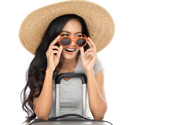 つば広の麦わら帽子とサングラスを身に着けている若いアジア女性の観光客。彼女は驚きを表明した。白い背景で隔離