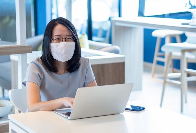 フェイスマスクを着用し、ビデオ通話や仕事にスマートフォンとラップトップを使用している若いアジア女性