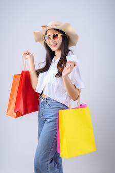안경과 모자를 착용하는 젊은 아시아 여성 흰색 배경에 많은 다채로운 쇼핑 가방과 함께 법안을 보유하고 있습니다.