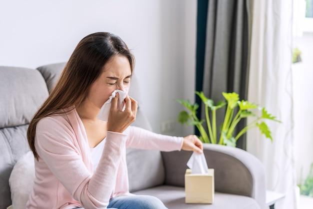 組織を使用して気分が悪くなり、自宅でくしゃみをするアレルギーを持つ若いアジアの女性