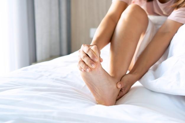 朝の足のけいれんを持つ若いアジアの女性。