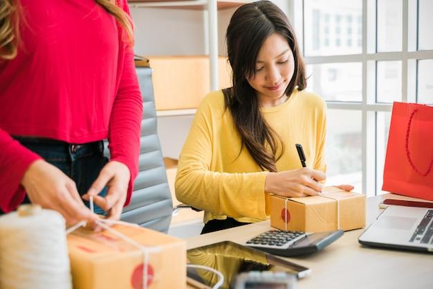 Молодые азиатские женщины работая совместно в офисе.