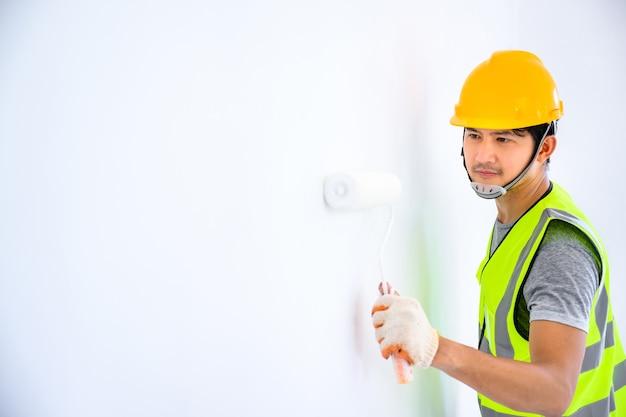 젊은 아시아 노동자 집의 벽을 칠하고 롤러를 사용하여 건설 현장에서 흰색 프라이머를 칠하는 화가로서