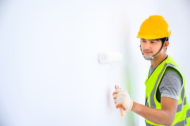 Young asian worker as a painter to paint the walls in the house and use a roller to paint the white primer on the construction site