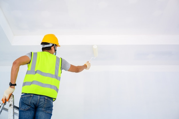 Young asian worker paint the ceiling inside the house and use a roller to paint the white primer on the construction site. Premium Photo