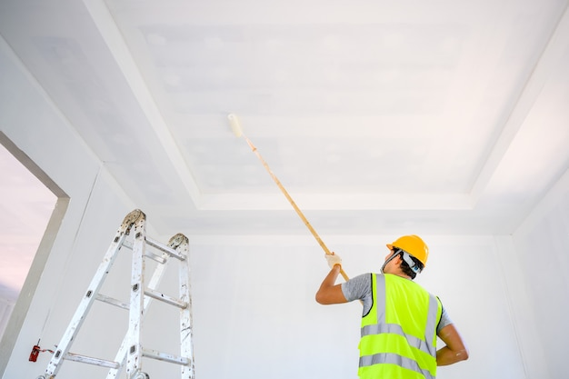 Young asian worker paint the ceiling inside the house and use a roller to paint the white primer on the construction site.