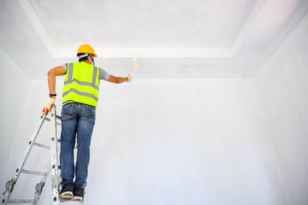Молодой азиатский рабочий покрасьте потолок внутри дома и с помощью валика нанесите белый грунт на строительной площадке.